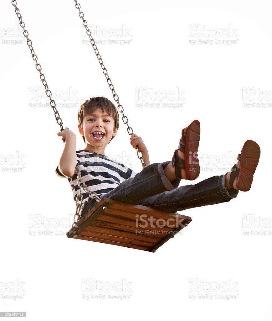 Boy having fun on a swing. stock photo