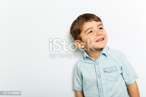 istock Boy having fun on studio grey background 1075108990