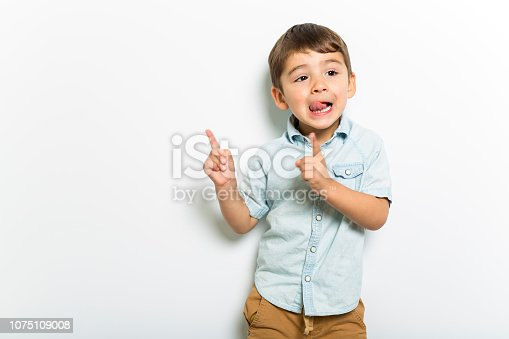 istock Boy having fun on studio grey background 1075109008