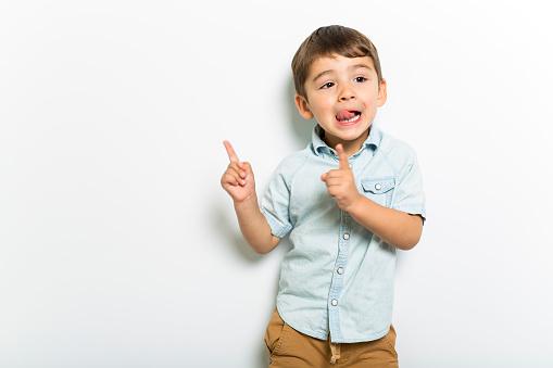 istock Boy having fun on studio grey background 1075109008
