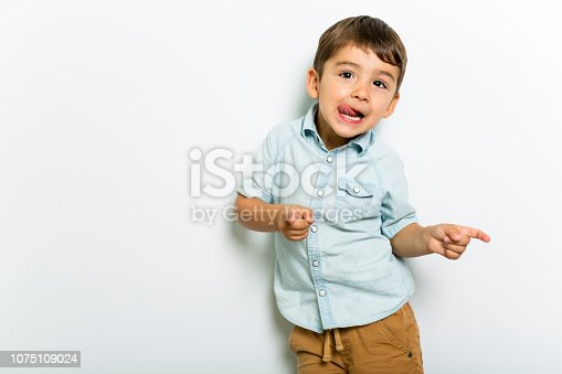 istock Boy having fun on studio grey background 1075109024