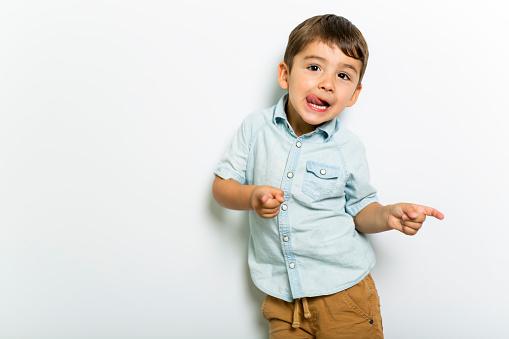 istock Boy having fun on studio grey background 1075109024