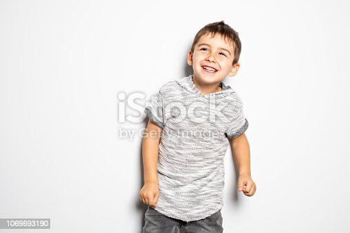istock Boy having fun on studio white background 1069693190