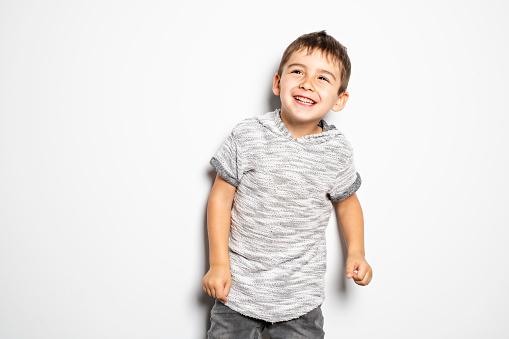 istock Boy having fun on studio white background 1069693190