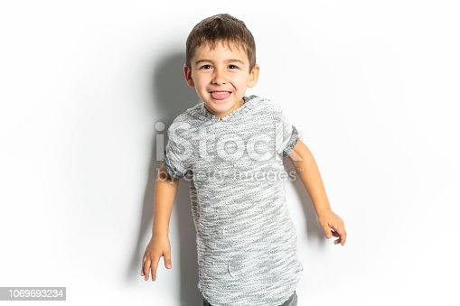istock Boy having fun on studio white background 1069693234