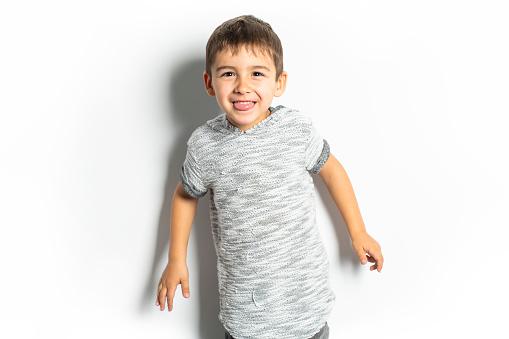 istock Boy having fun on studio white background 1069693234