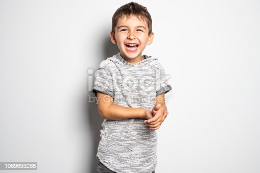 istock Boy having fun on studio white background 1069693268