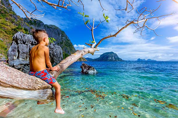Boy having fun on tropical beach stock photo