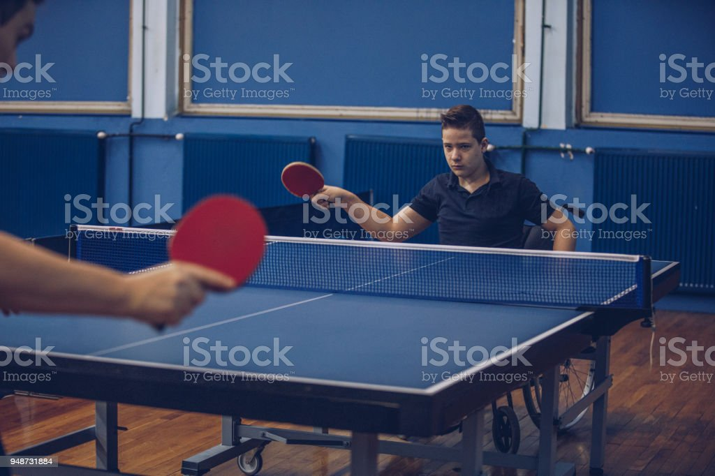 Young boy in a wheelchair playing table tennis