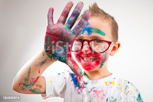 123499844 istock photo Boy having fun with finger paint 184935819