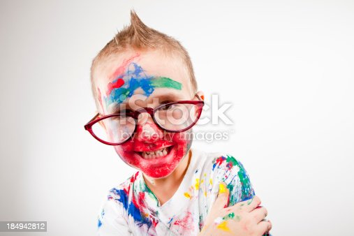 123499844 istock photo Boy having fun with finger paint 184942812