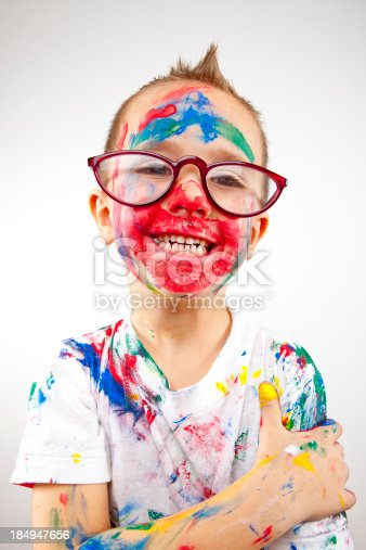 123499844 istock photo Boy having fun with finger paint 184947656