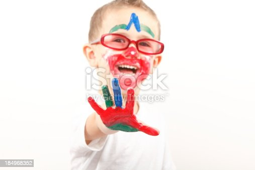 123499844 istock photo Boy having fun with finger paint 184968352