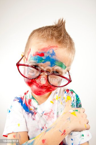 123499844 istock photo Boy having fun with finger paint 184992814