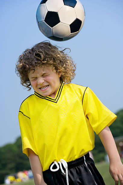 boy heading soccer ball - head injury stock photos and pictures