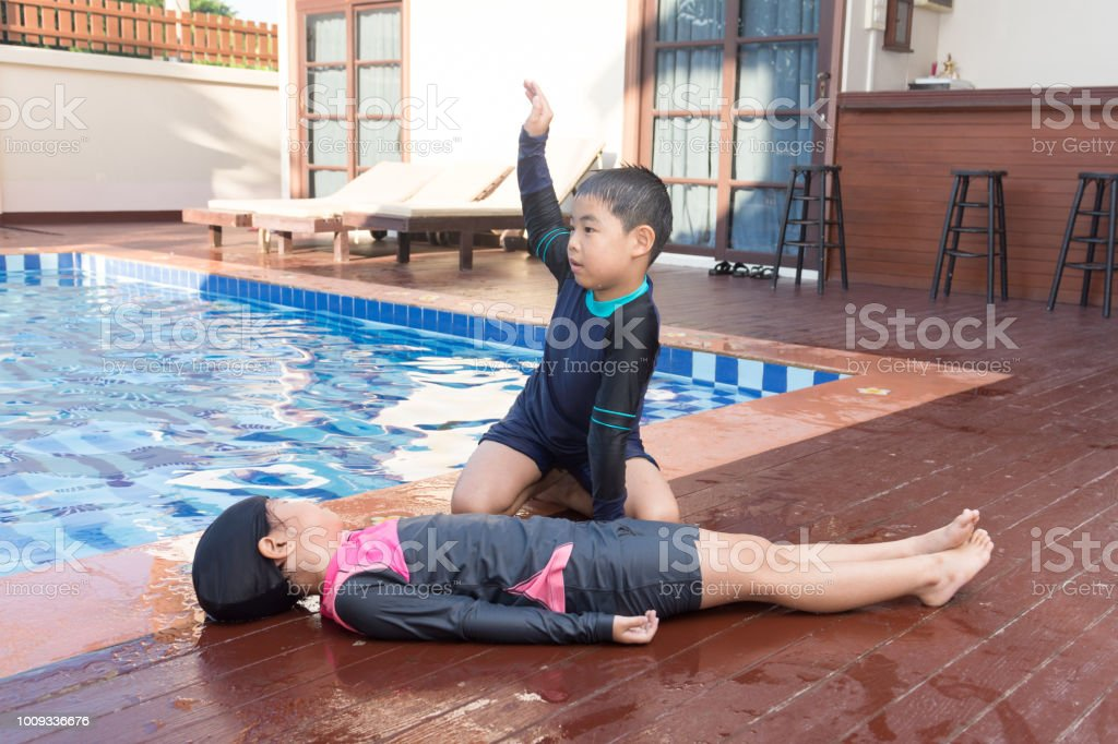 Boy helping drowning child girl in swimming pool by doing CPR. stock photo