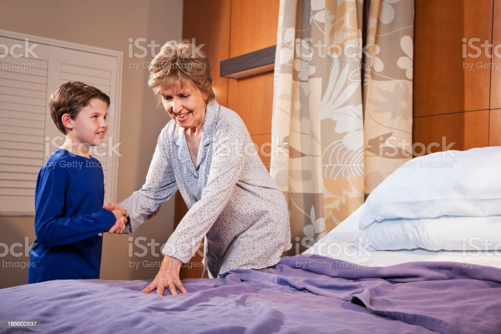 Boy helping grandmother in hospital room royalty-free stock photo