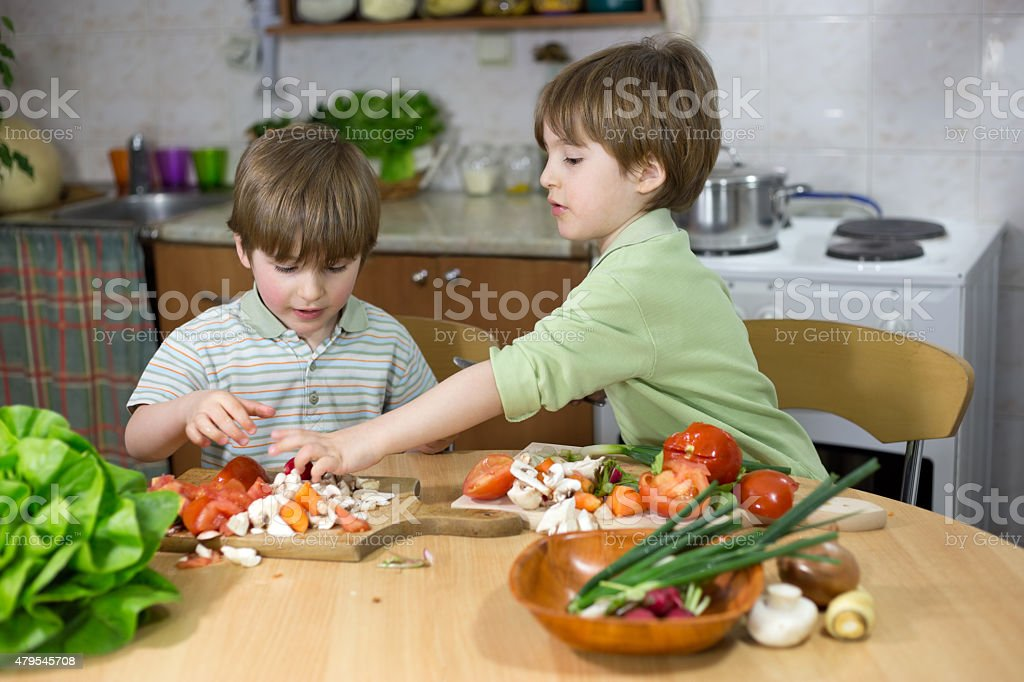 Boy Helping His Brother to Make Fresh Salad at Home stock photo