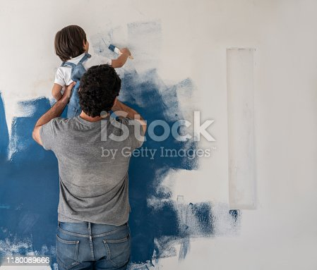 Boy helping his father painting the house blue using a brush - home improvement concepts