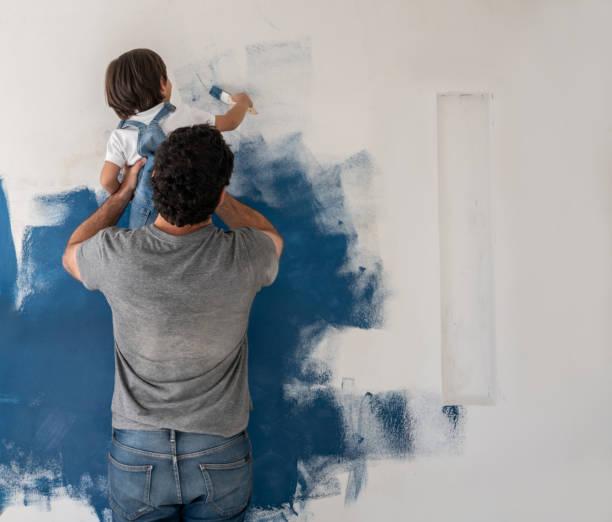 Junge hilft seinem Vater, das Haus zu malen – Foto