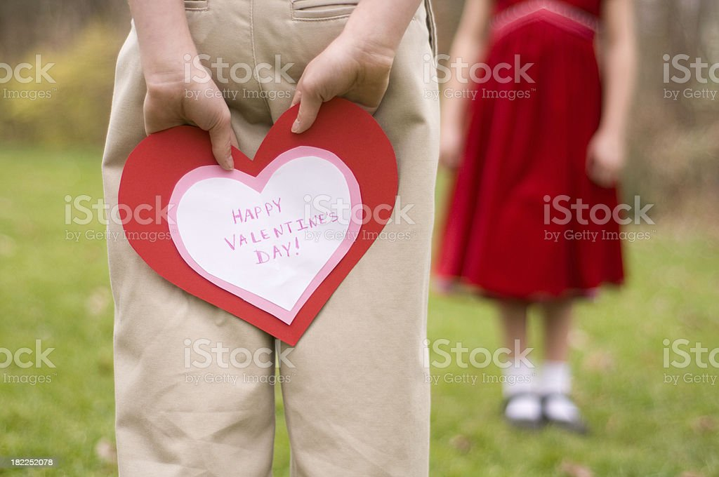 Boy hides Valentine's Day card behind back royalty-free stock photo