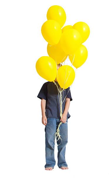 junge versteckt hinter einem haufen gelbe ballons in seiner hand - ballonhose stock-fotos und bilder