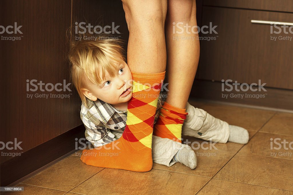 Boy hiding behind mother royalty-free stock photo