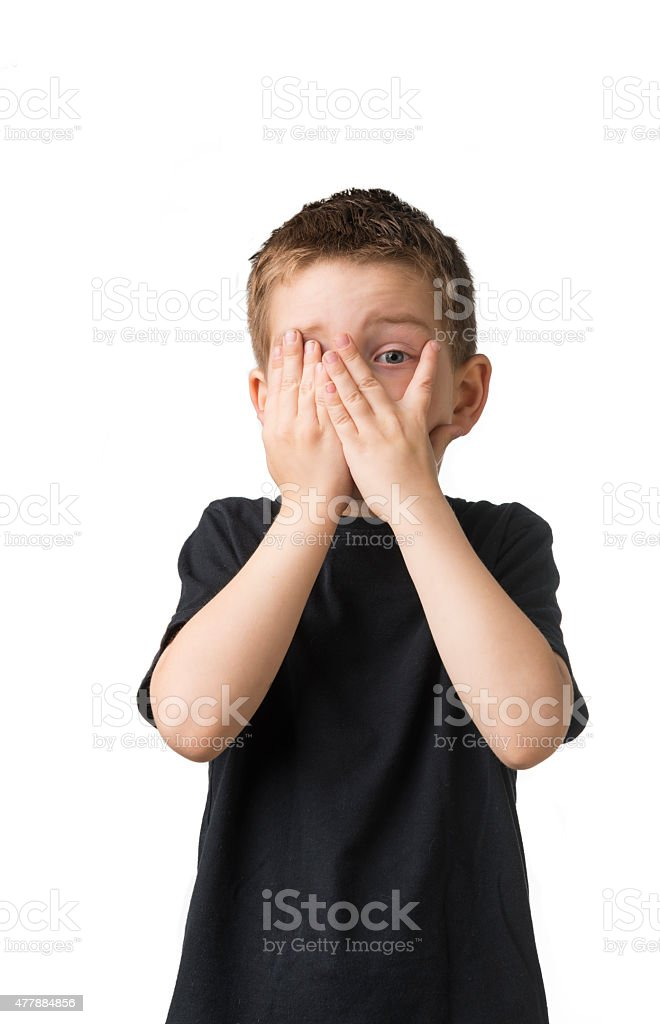 Boy hiding face with his hands stock photo