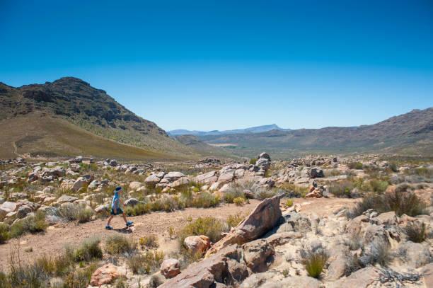 Muchacho solo de senderismo en una ruta en una zona montañosa del desierto - foto de stock