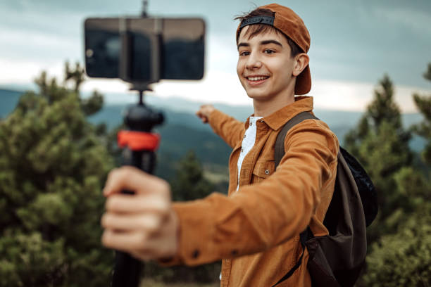 Boy hiking and vlogging using mobile phone stock photo