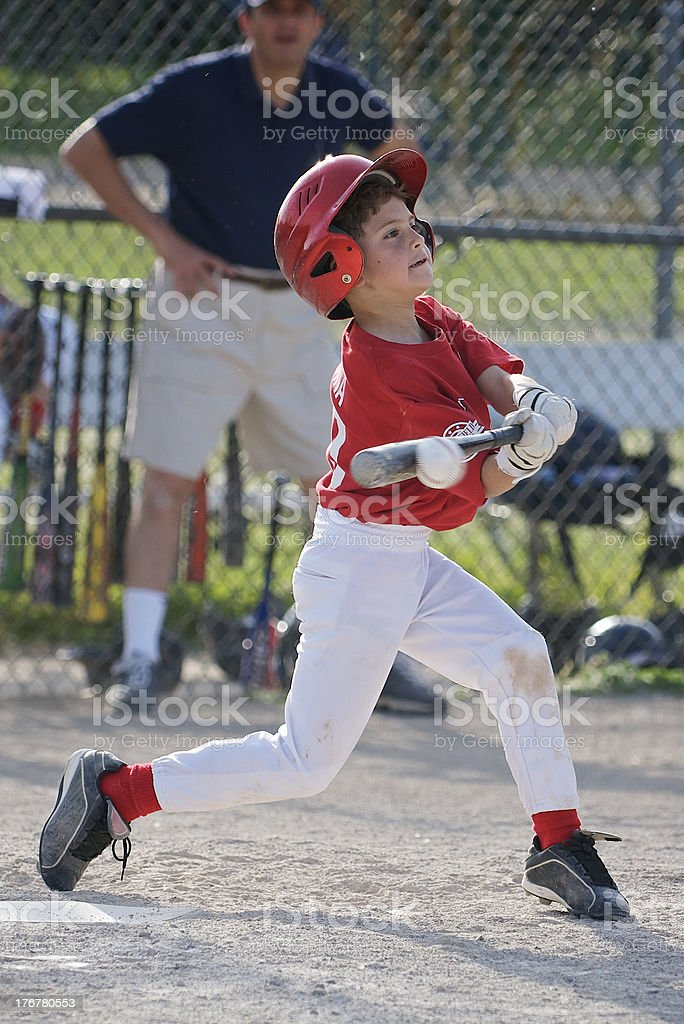 Boy hitting baseball, compressed on bat stock photo