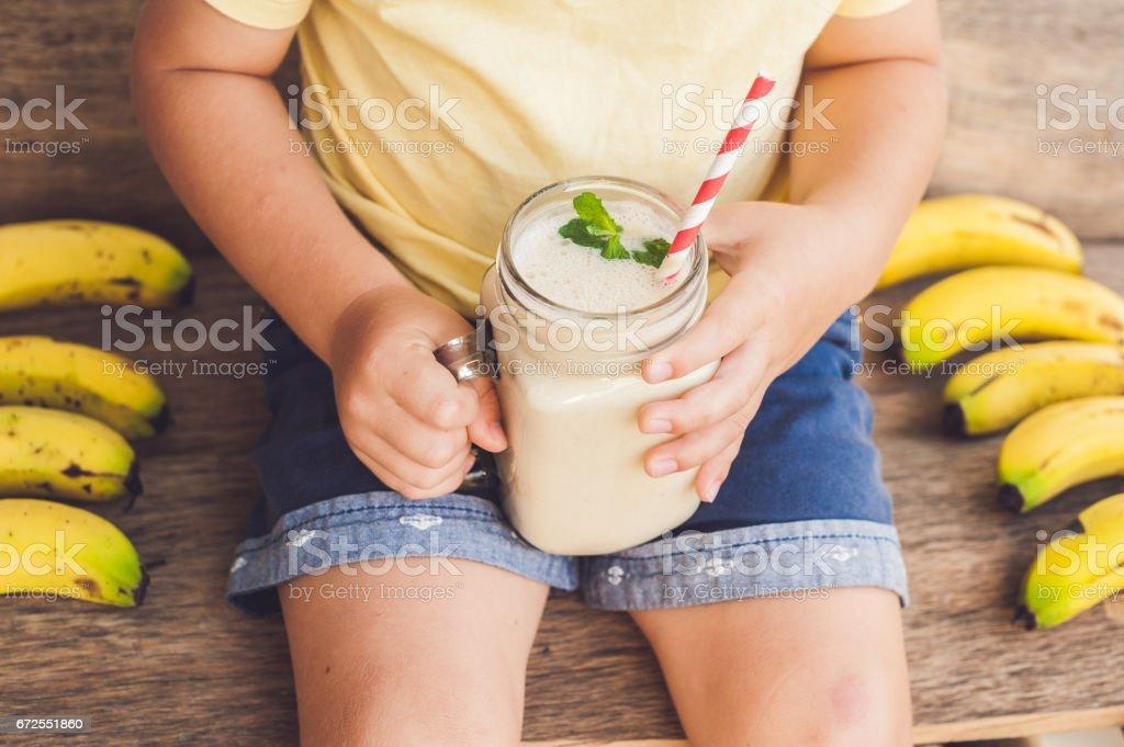 Boy holding a banana smoothie stock photo