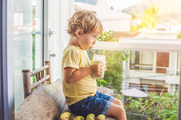junge hält einen bananen-smoothie - einmachglassmoothie stock-fotos und bilder