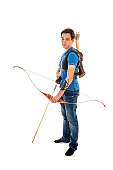 Boy with blue shirt and jeans standing with a longbow