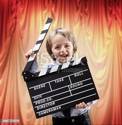 istock Boy holding a clapper board in a cinema theater 486732626