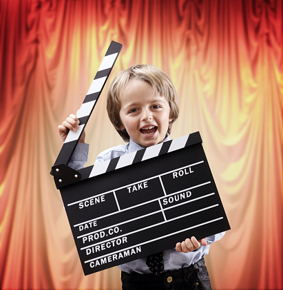 Boy or usher holding blank clapper board in a cinema theater concept for movie, action, film industry or theatrical performance