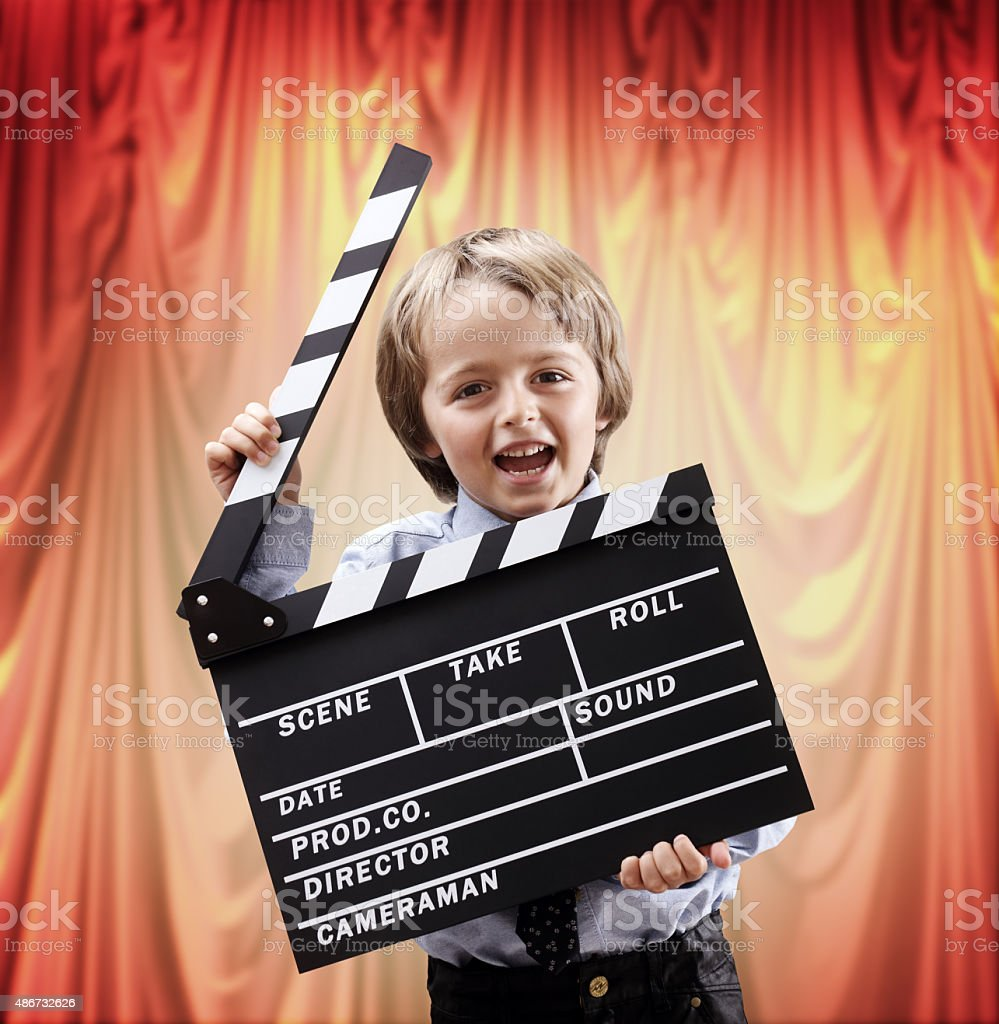 Boy holding a clapper board in a cinema theater stock photo