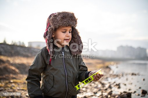A cute boy is holding a fishing line winder by the river on a sunny day