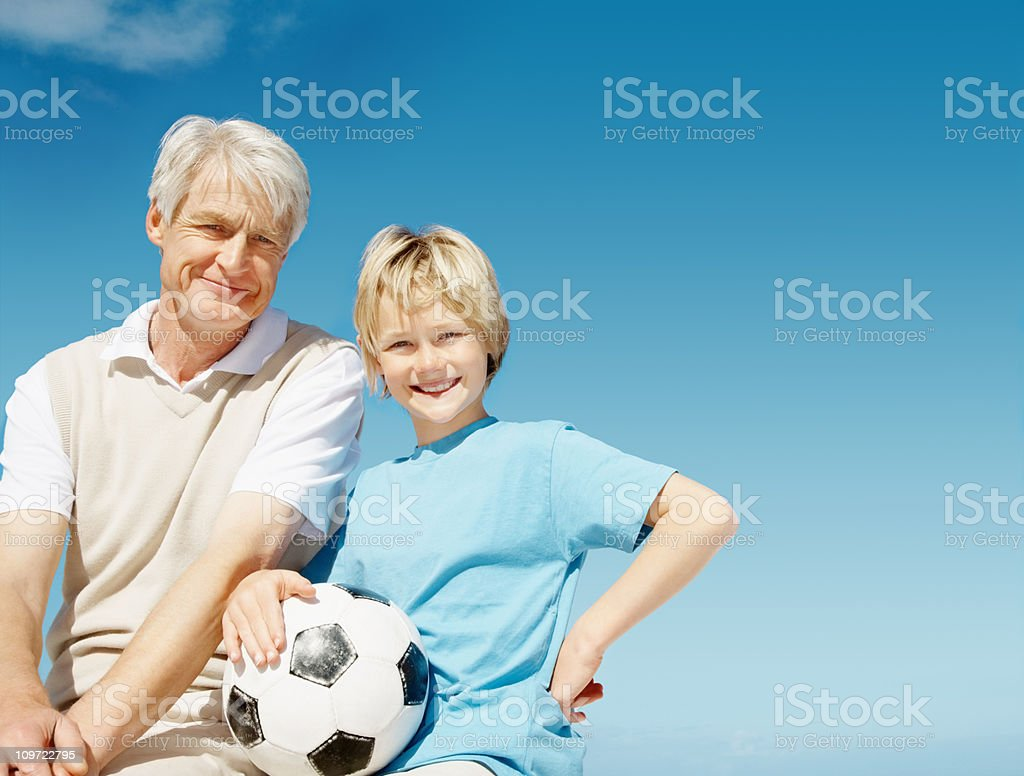 Boy holding a football and sitting with grandfather royalty-free stock photo