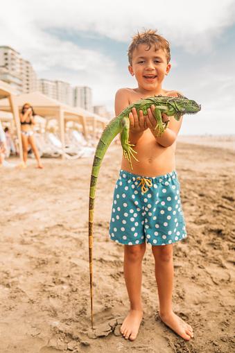 Boy holding a iguana at the beach