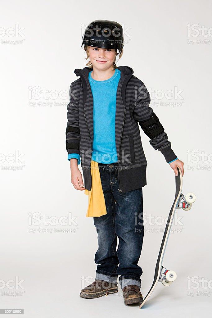 Ein Junge hält ein skateboard Lizenzfreies stock-foto