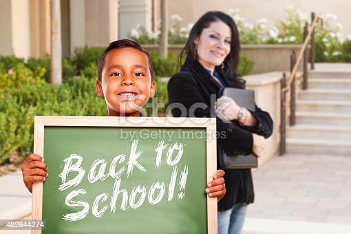 618753504 istock photo Boy Holding Back To School Chalk Board with Teacher Behind 482644274