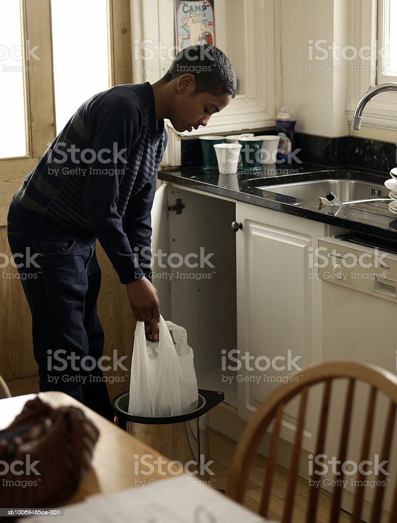 Boy (12-13) holding bag of waste in kitchen 免版稅 stock photo