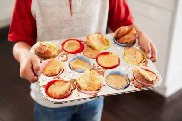 junge mit backblech, präsentieren die kuchen, die er zur kamera, mittelteil, gebacken hat hautnah - super torte stock-fotos und bilder