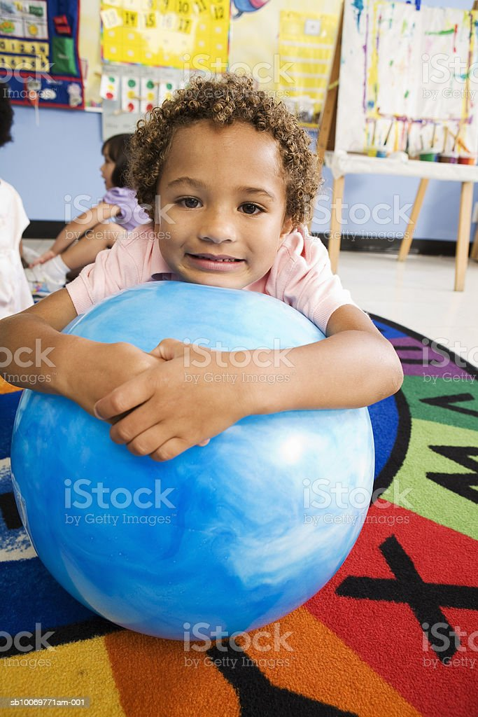 Boy (4-5) holding ball in classroom royalty-free stock photo