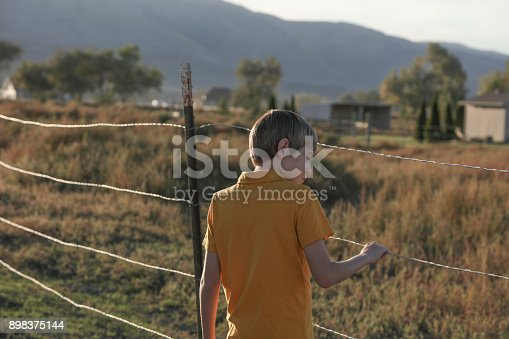 istock Boy holding barbed wire fence 898375144