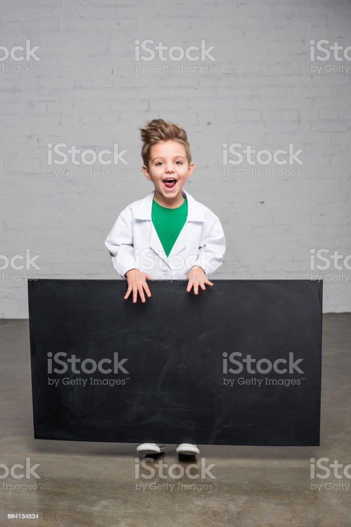 Boy holding blackboard royaltyfri bildbanksbilder