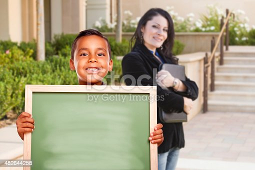 618753504 istock photo Boy Holding Blank Chalk Board on Campus with Teacher Behind 482644258