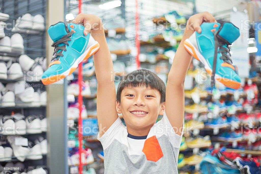 boy holding chosen shoes smiling in store stock photo