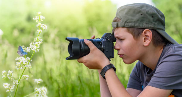 boy holding digitale camera en schieten vlinder op de wilde bloem - spiegelreflexcamera stockfoto's en -beelden